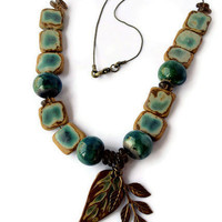 Green necklace with raku beads and brass leaf pendant on antique brass chain