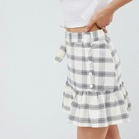 ASOS DESIGN mini skirt with side buttons in check at asos.com