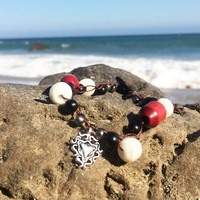 boho crocheted bracelet made with wooden beads, glass beads, and a heart charm clasped together with a vintage lucite button and tassel