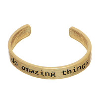 """Worn gold tone cuff bracelet stamped """"do amazing things""""."""