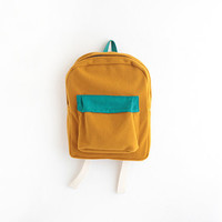 mustard wool backpack with turquoise pouch.