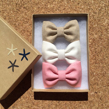 Tan, creamy off white, and pinky coral hair bows from seaside sparrow.