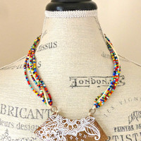 Large wood pendant with hand painted flowers  and seed bead glass cording necklace.
