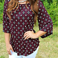 Our Addicted To Love Top is perfect for Game Days! It is Black and Burgundy in Color with a Quatrefoil design throuhgout. It features 3/4 bell sleeves, and an elastic neckline that can be worn off the shoulder.