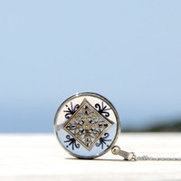 Metal echoes IX, round kinetic pendant with double sided silver lotus flower with hand drawn black adornments, encased in resin