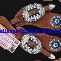 Medium oil spur straps. Cart buckles and two 1-1/2 inch antique conchos. Capri Blue and Clear Swarovski crystals.