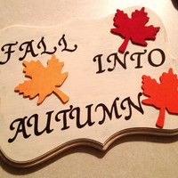 "hand made and hand painted rustic looking fall home decoration saying ""Fall into Autumn"" with tricolored fall leaves"