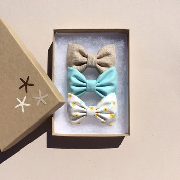 Tan, aqua, and yellow daisy hair bow set from Seaside Sparrow. These hair bows make a perfect gift for her.