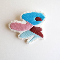 Hand embroidered brooch with unique geometric design using blues, pink and maroon cotton thread An Astrid Endeavor textile fashion jewelry