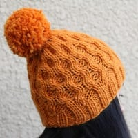 Knit honeycomb hat for women with cables and pompom in orange color