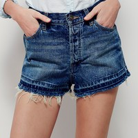 High rise denim cutoff shorts with raw fringed hem. Five-pocket styling and button-fly closure. Released hem for a flattering fit. Pair with embroidery lace top, gladiator sandals, floppy hat & fringe crossbody bag.