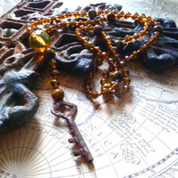 Amber colored, rosary inspired beaded necklace with small rusty key