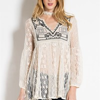 Sheer delicate novelty lace babydoll tunic featuring a embroidered design and long bubble sleeves with an elastic cuff, plunging v-neckline, and finish with pleated flare detailing. Pair with cami, skinny jeans, lace up shoes.