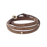 """Brown leather wrap bracelet with gold tone studs stamped """"Enjoy the journey""""."""