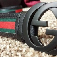 Men's black Gucci belt with green and red strip.