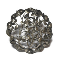 Large circle brooch, flowers leaves vine their way through this silver tone large intricate open work and etched pin, twined ribbon edging