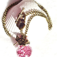 Round glass orb necklace filled with delicate pink fiber beads, hearts and bronze chain