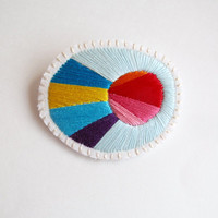 Hand embroidered brooch with colorful bursts of blues, pinks, orange, yellow, red and purple on cream muslin with cream felt backing