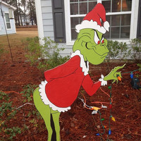 Grinch steals christmas yard decoration.