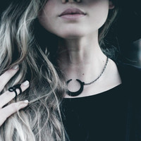 Eclipse necklace in black - A necklace with the Sun and Moon hiding from each other. Runes capture the last light.